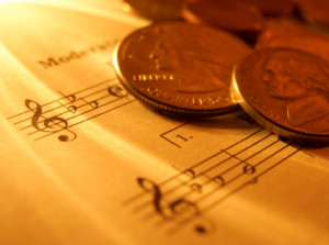 gold coins on a music score (image)